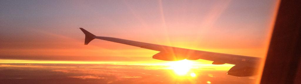 Flieger fliegt richtung untergehenden Sonne