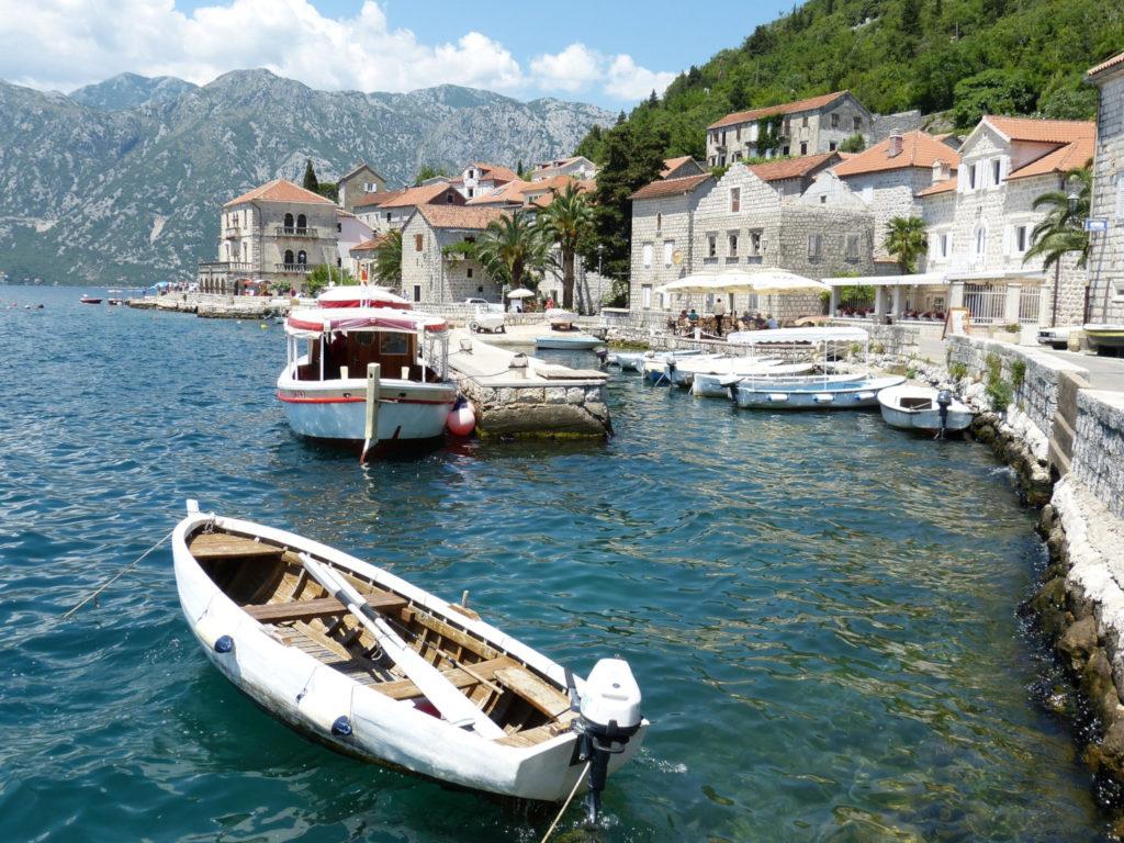 Die Bucht von Kotor in Montenegro. Fischerboote, klares blaues Wasser, weiße Steinhäuser, Berge an den Ufern und an der Küste.