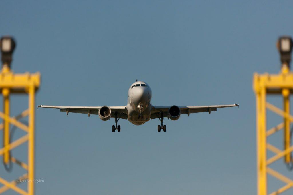 Weißes Passagier-Flugzeug im Landeanflug auf einen Flughafen. Von vorne aufgenommen.