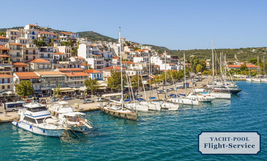 Hafen von Skiathos in Griechenland. Segelyachten und Boote am Hafenkai. Häuser hinter dem Hafen an den Berg gebaut. Sonne. Blaues Wasser. Urlaub