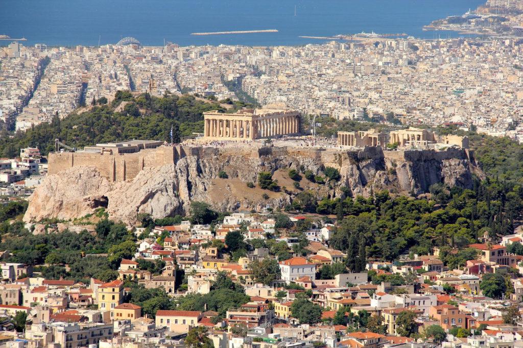 Akropolis in Athen. Säulentempel auf einem Bergplateau über der Stadt. Im Hintergrund das Meer.