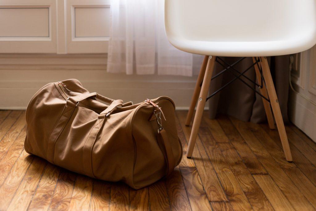 Reisetasche gepackt auf dem Boden in der Wohnung.
