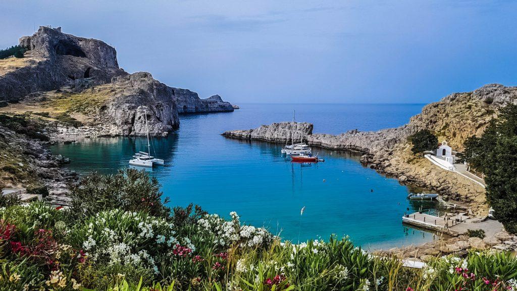 Segelyachten in einer Bucht. Glasklares Wasser, strahlend blauer Himmel. Blumen und Felsen