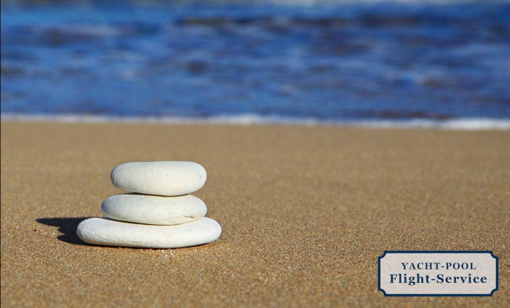 Kleiner Steinhaufen am Meer mit leichten Wellen im Hintergrund
