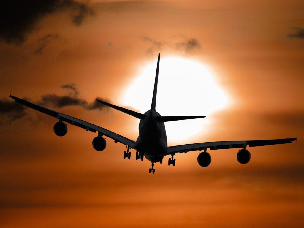 Flugzeug startet in der Abenddämmerung. Vor untergehenden Sonne.