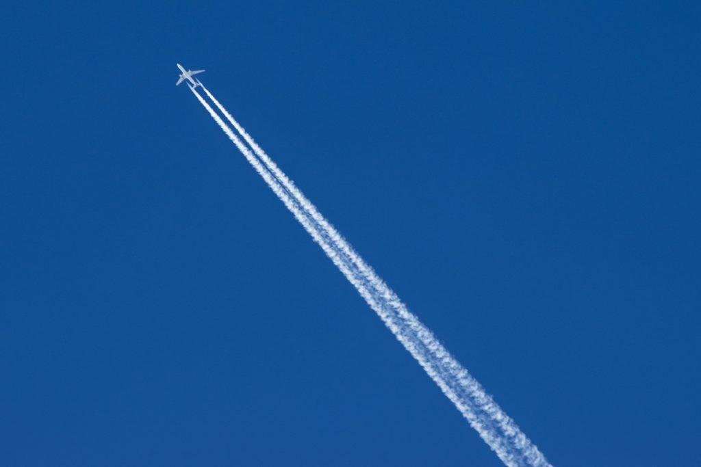 Flugzeug am blauen Himmel mit Kondenzstreifen.