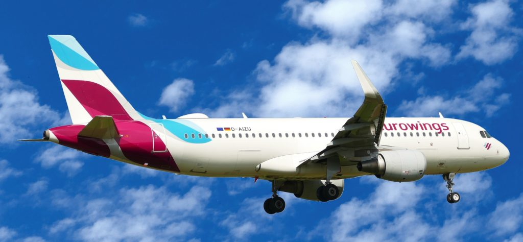 Flugzeug Maschine von Eurowings mit ausgefahrenem Fahrwerk beim Landeanflug. Im Hintergrund leichte weiße Schleierwolken.