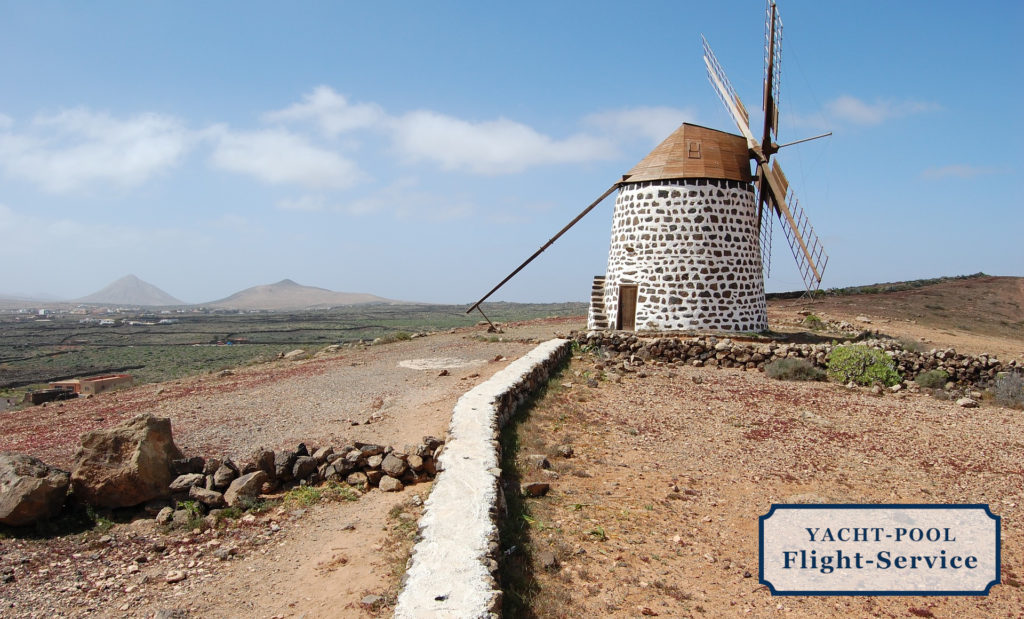 Windmühle auf einer Insel der Kanaren. Mit Steinmauer im Vordergrund und wulkanischem, braunen Boden