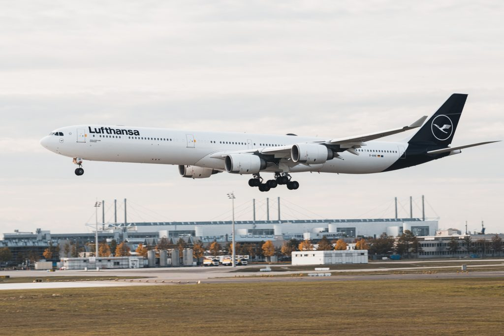 Vierstrahliges Lufthansa Flugzeug im neuen blauen Design beim Landeanflug. Mit ausgefahrenem Fahrwerk.