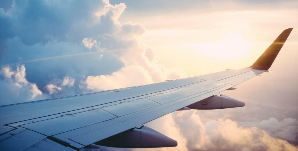 Blick aus dem Flugzeug über den Wolken. Flugzeugtragfläche über den Wolken mit Sonne im Hintergrund.