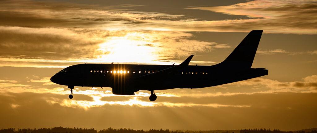 Flugzeug im Landeanflug. Am Abend. Sonne geht im Hintergrund unter. Sonnenstrahlen scheinen durch die Flugzeugfenster